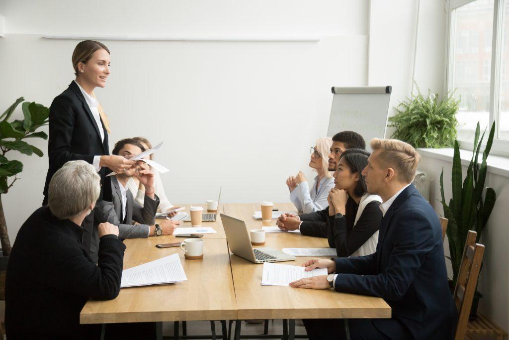 Successful female boss leading team meeting talking to multiraci