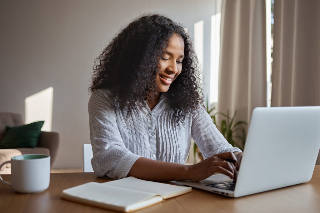 Attractive positive young Afro American woman freelancer working